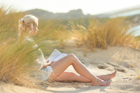 well  being: Relaxed woman enjoys reading on beautiful sandy beach.  Young lady with book in her hand. Concept of happiness, enjoyment and well being.  Enjoying Sun on Vacations. Foto de archivo