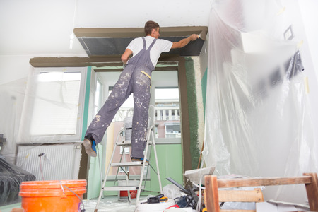 stucco house: Thirty years old manual worker with wall plastering tools inside a house. Plasterer renovating indoor walls and ceilings with float and plaster. Stock Photo