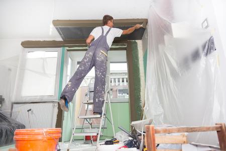 Trente ans ouvrier mur avec des outils de plâtrage intérieur d'une maison. Plâtrier rénovation des murs intérieurs et des plafonds avec flotteur et plâtre.