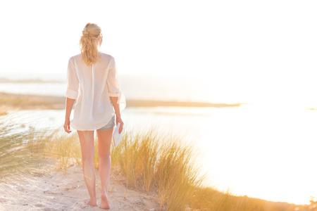 자유와 생명 아름다운 모래 해변을 즐기는 편안한 여자. 무료 편안하고 행복한 기분이 젊은 아가씨. 행복, 즐거움과 웰빙의 개념입니다. 휴가에 일을