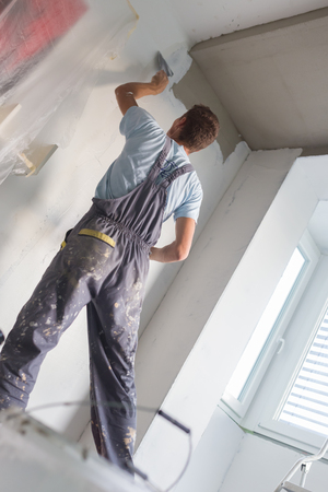 indoor inside: Thirty years old manual worker with wall plastering tools inside a house. Plasterer renovating indoor walls and ceilings with float and plaster. Stock Photo