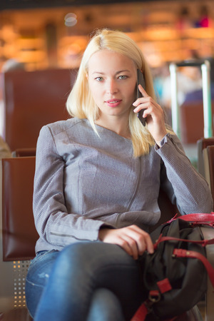 enabling: Casual blond young woman calling by cell phone while waiting to board a plane at the departure gates. Wireless network hotspot enabling people to access internet conection. Public transport.