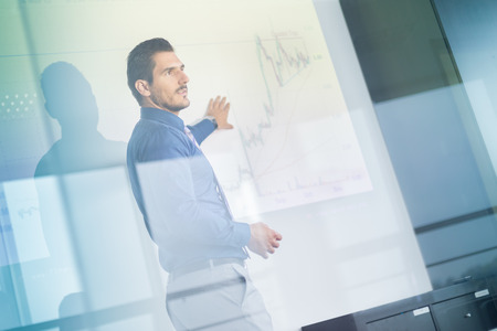 boardroom: Business man making a presentation in front of whiteboard. Business executive delivering a presentation to his colleagues during meeting or in-house business training. View through glass.