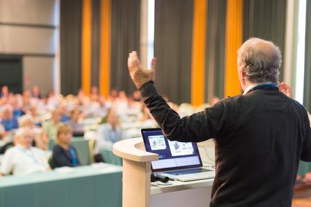 reuniones empresariales: Ponente en la Conferencia de negocios con presentaciones públicas. Audiencia en la sala de conferencias. Negocios y Emprendimiento concepto. Vista trasera. Composición panorámica. Desenfoque de fondo.