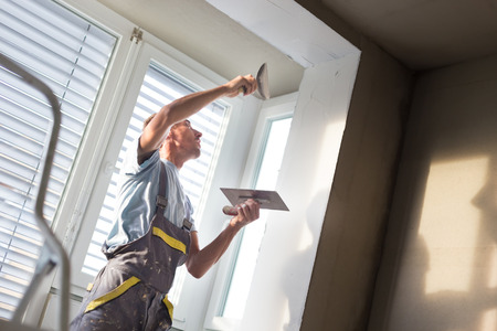 plasterer: Thirty years old manual worker with wall plastering tools inside a house. Plasterer renovating indoor walls and ceilings with float and plaster. Stock Photo