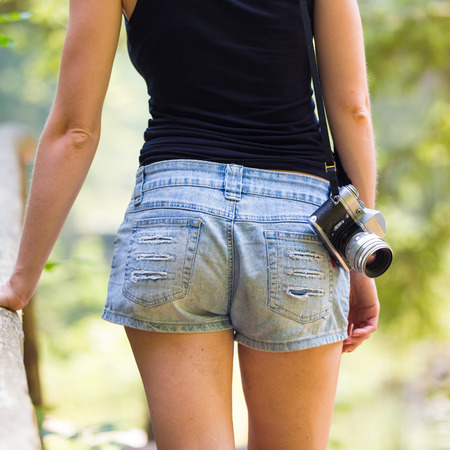 sexy woman: Rear body crop of a hipster girl wearing jeans shorts an sporty black sleeveless t-shirt, walking in nature, carrying vintage camera over her shoulder. Healthy active lifestyle. Square composition. Stock Photo