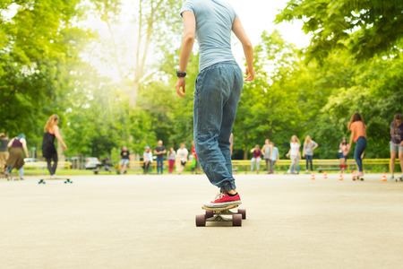 Teenage girl wearing blue jeans and sneakers practicing long board riding in skateboarding park. Active urban life. Urban subculture.