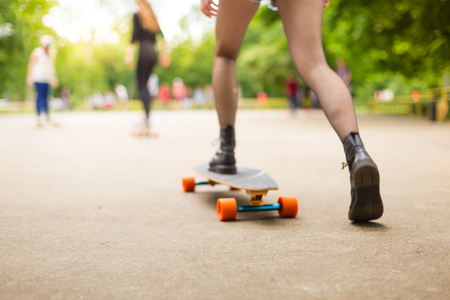 subculture: Teenage girl wearing black boots and stockings practicing long board riding outdoors in skateboarding park. Active urban life. Urban subculture. Motion blured. Focus on the floor for copy space. Stock Photo