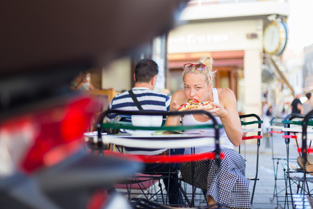 Casual blond lady eating pizza slice outdoor in typical italian street restaurant on hot summer day. Traditional italian fast food eatery.