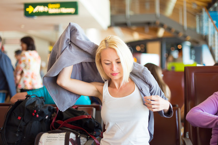 destinations: Casual blond young woman feeling cold and putting on her jacket while waiting to board a plane at the departure gates. Air condition on public transport.