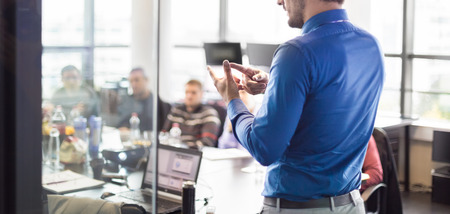 training session: Business man making a presentation at office. Business executive delivering a presentation to his colleagues during meeting or in-house business training, explaining business plans to his employees. Stock Photo
