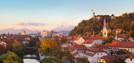 karavanke: Cityscape of the Slovenian capital Ljubljana at sunset. Ljubljana castle on hill above town. River Ljubljanica running trough city center. Karavanke mountains in background. Panorama.