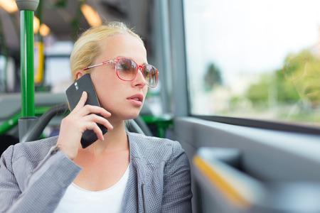 fila de personas: Rubia caucásico mujer de negocios hablando por teléfono celular, viajando en autobús. El transporte público y los desplazamientos al trabajo.