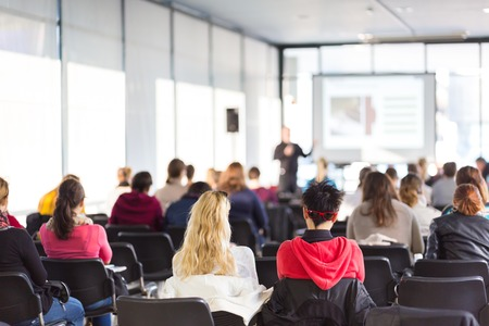 course: Speaker giving presentation in lecture hall at university. Participants listening to lecture and making notes. Stock Photo