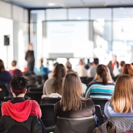 Lautsprecher, der Darstellung im Hörsaal an der Universität. Die Teilnehmer hören einen Vortrag und machte sich Notizen. Standard-Bild - 47465380