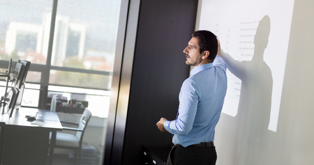 white board: Business man making a presentation in front of whiteboard. Business executive delivering a presentation to his colleagues during meeting or in-house business training. Stock Photo