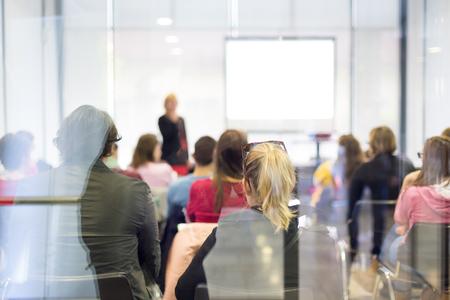 Referent einen Vortrag bei Geschäftstreffen. Trog die Glasrücksicht auf Publikum in Hörsaal. Business and Entrepreneurship