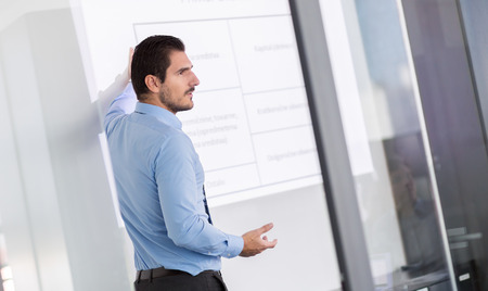 office presentation: Business man making a presentation in front of whiteboard. Business executive delivering a presentation to his colleagues during meeting or in-house business training. Stock Photo