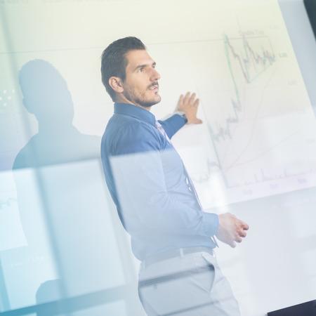 Geschäftsmann bei einem Vortrag vor der Whiteboard. Geschäftsmann liefert eine Präsentation an seine Kollegen während der Sitzung oder in-house Business-Training. Blick durch Glas.