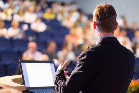 estudiando: Ponente en la Conferencia de negocios con presentaciones p�blicas. Audiencia en la sala de conferencias. Club de Emprendimiento. Vista trasera. Composici�n Horisontal. Desenfoque de fondo.