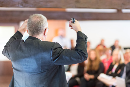training business: Business man leading a business workshop. Corporate executive delivering a presentation to his colleagues during meeting or in-house business training. Business and entrepreneurship concept.