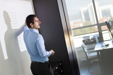 Business man making a presentation in front of whiteboard. Business executive delivering a presentation to his colleagues during meeting or in-house business training. Stock Photo