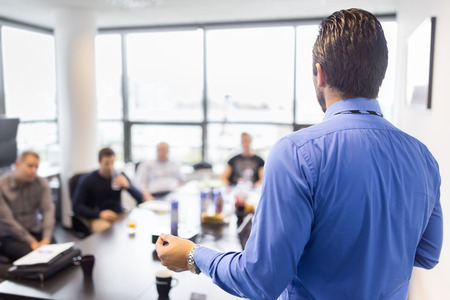 Business man making a presentation at office. Business executive delivering a presentation to his colleagues during meeting or in-house business training, explaining business plans to his employees. Stockfoto