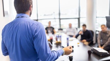 speaking: Business man making a presentation at office. Business executive delivering a presentation to his colleagues during meeting or in-house business training, explaining business plans to his employees. Stock Photo