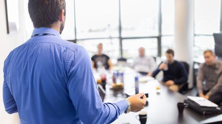 L'homme d'affaires de faire une présentation au bureau. Dirigeant d'entreprise de présenter un exposé à ses collègues lors de la réunion ou de formation interne de l'entreprise, expliquant les plans d'affaires à ses employés. Banque d'images - 47484931