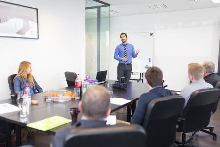 utbildning: Affärsman gör en presentation på kontoret. Företagsledare levererar en presentation till sina kollegor under möte eller egen affärsutbildning, och förklarar affärsplaner för sina anställda. Stockfoto