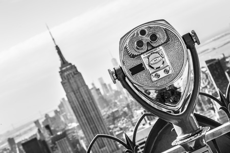 New York City, USA. Vintage tourist binoculars at Top of the Rock observation deck in front of Manhattan downtown skyline with Empire State Building and skyscrapers at sunset. Black and white.