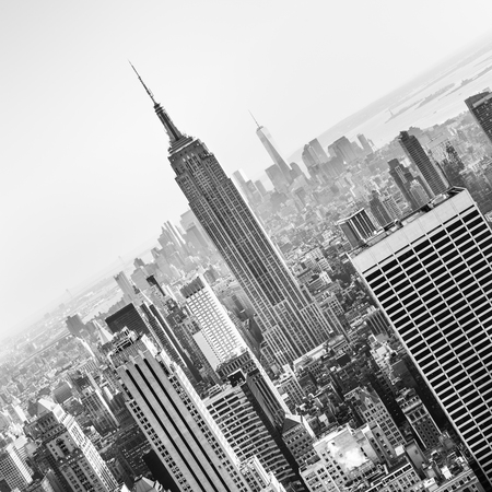square image: New York City. Manhattan downtown skyline with illuminated Empire State Building and skyscrapers at sunset. Vertical composition. Black and white image. Square composition.