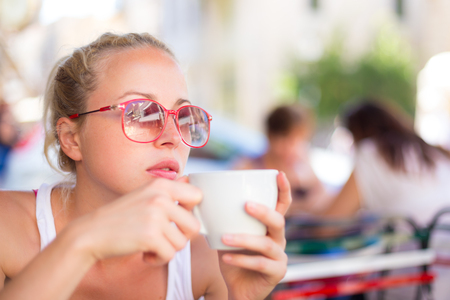 espresso: Calm casual blond lady enjoying cup of coffee outdoor in typical italian  street coffee house on warm summer day.