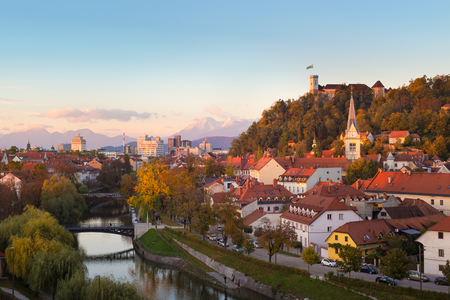 karavanke: Cityscape of the Slovenian capital Ljubljana at sunset. Ljubljana castle on hill above town. River Ljubljanica running trough city center. Karavanke mountains in background.