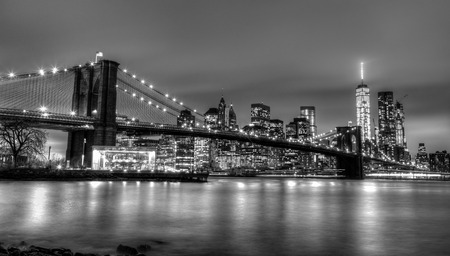 hudson river: Brooklyn bridge and New York City Manhattan downtown skyline at dusk with skyscrapers illuminated over East River panorama. Copy space. Black and white image.