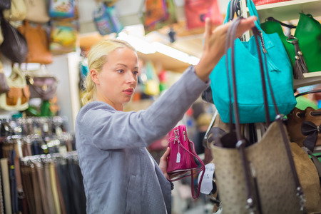 casually dressed: Beautiful casually dressed caucasian blond woman shopping for colorful new leather purse in fashion boutique.