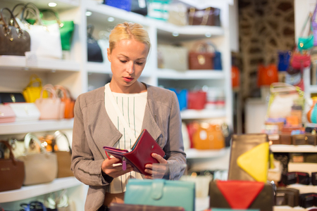 casually dressed: Beautiful casually dressed caucasian blond woman shopping for new colorful stylish leather wallet in fashion boutique. Stock Photo