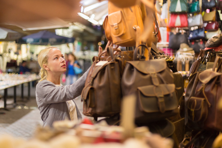 shopper: Beautiful casually dressed caucasian blond woman shopping for new leather bag on crafts market in Chania, Crete, Greece.