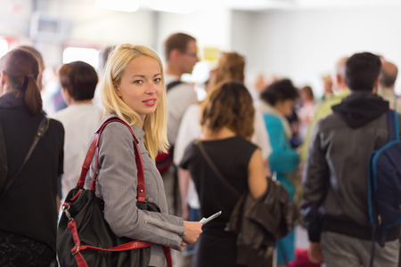 to queue: Young blond caucsian woman waiting in line with plain ticket in her hands. Lady standing in a long queue to board a plane.