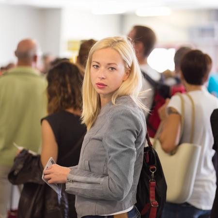 file d attente: Jeune femme blonde de caucsian attendre en ligne avec le billet ordinaire dans ses mains. Lady debout dans une longue file d'attente à bord d'un avion.