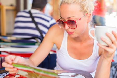 restaurante italiano: Calma ocasional señora rubia con gafas de sol de moda, disfrutando de una taza de café mientras se comprueba en el típico menú de cafetería calle italiano o restaurante el día de verano caliente.