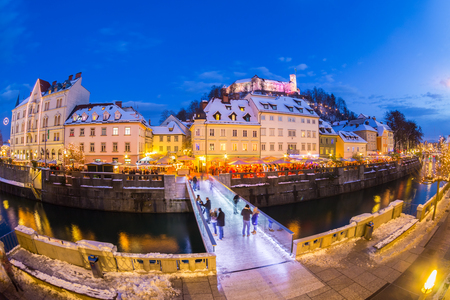 fish eye lens: Ljubljana in Christmas time. Lively nightlife in old medieval city center decorated with Christmas lights. Slovenia, Europe. Shot at dusk with fish eye lens. Stock Photo