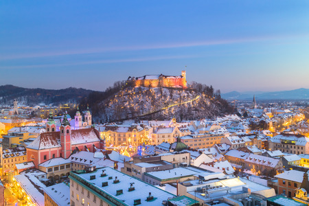 Aerial panoramic view of Ljubljana decorated for Christmas holidays. Roofs covered in snow in winter time. Slovenia, Europe.