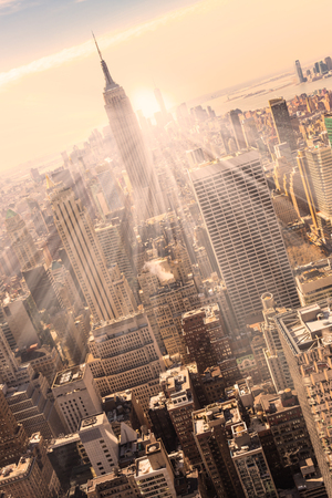 empire state building: New York City. Manhattan downtown skyline with illuminated Empire State Building and skyscrapers at sunset. Vertical composition. Warm evening colors. Stock Photo