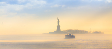 statue: Staten Island Ferry cruises past the Statue of Liberty on a misty sunset. Manhattan, New York City, United States of America. Panoramic composition. Copy space. Stock Photo