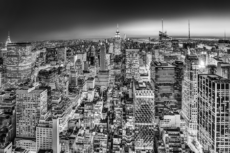 business center: New York City. Manhattan downtown skyline with illuminated Empire State Building and skyscrapers at dusk. Black and white image. Stock Photo