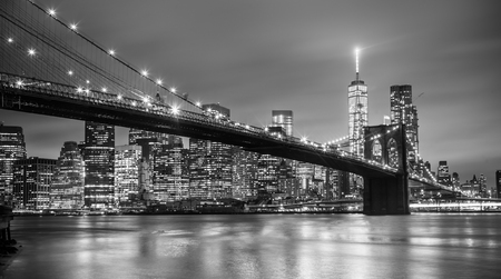 cities: Brooklyn bridge and New York City Manhattan downtown skyline at dusk with skyscrapers illuminated over East River panorama. Copy space. Black and white image.