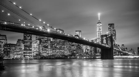 fondo blanco y negro: Puente de Brooklyn y horizonte de la ciudad de Nueva York Manhattan en la oscuridad con los rascacielos iluminados en el East River panorama. Copiar el espacio. Imagen blanco y negro. Foto de archivo