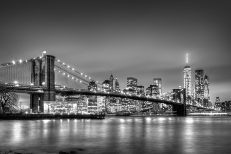 over white: Brooklyn bridge and New York City Manhattan downtown skyline at dusk with skyscrapers illuminated over East River panorama. Copy space. Black and white image.