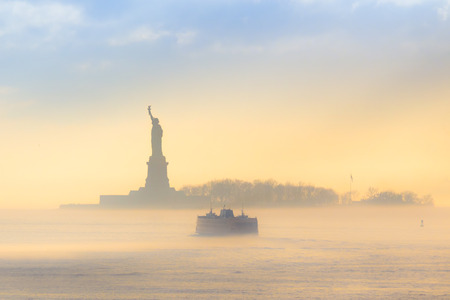 Staten Island Ferry cruises past the Statue of Liberty on a misty sunset. Manhattan, New York City, United States of America.